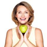 Jeune femme de sourire heureuse avec la pomme verte Photos stock
