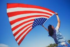 Jeune femme de sourire heureuse avec le drapeau américain national contre le ciel bleu photo stock