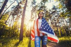 Jeune femme de sourire heureuse avec le drapeau américain national dehors photos stock