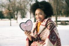 Jeune femme de sourire heureuse avec le grand coeur dans le jour d'hiver Photo libre de droits