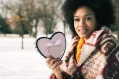 Jeune femme de sourire heureuse avec le grand coeur dans le jour d'hiver Photographie stock