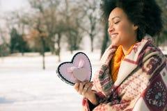 Jeune femme de sourire heureuse avec le grand coeur dans le jour d'hiver Images stock