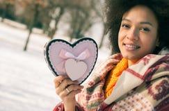 Jeune femme de sourire heureuse avec le grand coeur dans le jour d'hiver Photo stock