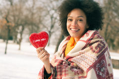 Jeune femme de sourire heureuse avec le grand coeur rouge dans le jour d'hiver Photographie stock