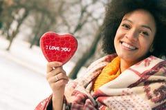 Jeune femme de sourire heureuse avec le grand coeur rouge dans le jour d'hiver Images stock
