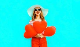 Jeune femme de sourire heureuse avec les ballons à air en forme de coeur rouges dans le chapeau de paille d'été et shorts sur le  photographie stock libre de droits