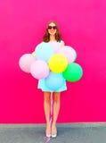 Jeune femme de sourire heureuse avec les ballons colorés d'un air ayant l'amusement en été au-dessus d'un fond rose images libres de droits
