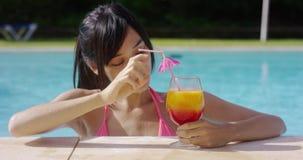 Jeune femme de sourire heureuse avec un cocktail fruité clips vidéos