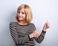 Jeune femme de sourire heureuse blonde montrant le pouce vers le haut du signe par deux Han Photo stock