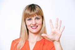 Jeune femme de sourire heureuse d'affaires affichant cinq doigts Photo libre de droits