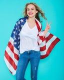 Jeune femme de sourire heureuse dans les jeans et le T-shirt blanc enveloppés dans un drapeau américain, faisant le signe de paix Images stock