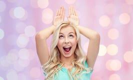 Jeune femme de sourire heureuse faisant des oreilles de lapin Photo stock