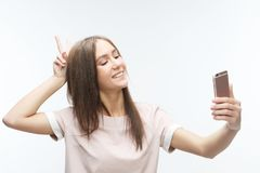 Jeune femme de sourire heureuse portant prenant le selfie avec le smartphone photographie stock