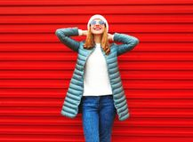 Jeune femme de sourire heureuse sur un fond rouge Image stock