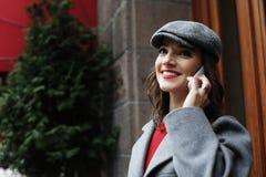 Jeune femme de sourire invitant le smartphone sur la rue de ville images stock