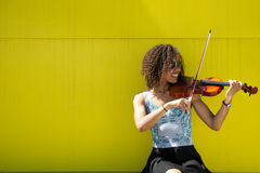 Jeune femme de sourire jouant le violon dehors Photographie stock libre de droits