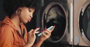 Jeune femme de sourire ? l'aide du smartphone ? la laverie automatique Blanchisserie publique de libre service clips vidéos