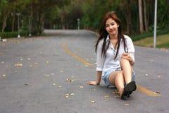 Jeune femme de sourire la reposant sur la route goudronnée ` s heureux et vrai photo libre de droits