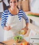 Jeune femme de sourire mélangeant la salade fraîche Photos libres de droits