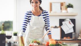 Jeune femme de sourire mélangeant la salade fraîche Photos stock
