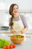 Jeune femme de sourire mélangeant la salade fraîche images stock