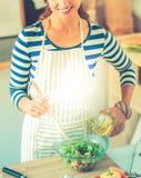 Jeune femme de sourire mélangeant la salade fraîche, bureau proche debout Image stock