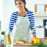 Jeune femme de sourire mélangeant la salade fraîche, bureau proche debout Photographie stock