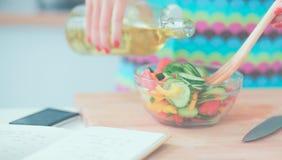 Jeune femme de sourire mélangeant la salade fraîche dans la cuisine Photos stock