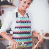 Jeune femme de sourire mélangeant la salade fraîche dans la cuisine Images stock