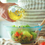 Jeune femme de sourire mélangeant la salade fraîche, tenant la bouteille d'huile Photo stock