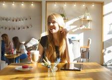 Jeune femme de sourire magnifique regardant directement la caméra tout en buvant du café et mangeant le gâteau en café photographie stock