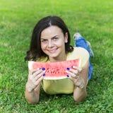 Jeune femme de sourire mangeant la pastèque Image libre de droits