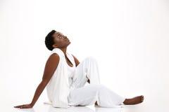 Jeune femme de sourire mignonne d'afro-américain s'asseyant et recherchant Photo stock