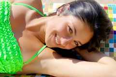 Jeune femme de sourire mignonne dans le bikini sur le plan rapproché heureux de banc coloré Photographie stock