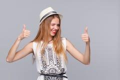 Jeune femme de sourire montrant des pouces, sur le fond gris Fille heureuse clignant de l'oeil joyeux image stock