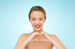 Jeune femme de sourire montrant le signe de main de forme de coeur Photographie stock libre de droits