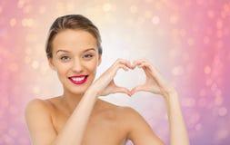 Jeune femme de sourire montrant le signe de main de forme de coeur Image stock