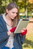 Jeune femme de sourire occupée avec Apple Ipad Images stock