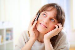 Jeune femme de sourire parlant au téléphone Photo stock