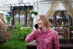 Jeune femme de sourire parlant du téléphone dans le restaurant de rue Photographie stock libre de droits