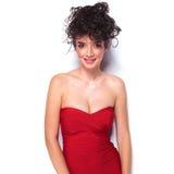 Jeune femme de sourire portant une robe rouge sexy photographie stock libre de droits