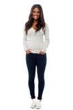Jeune femme de sourire posant avec des mains dans des poches Images stock