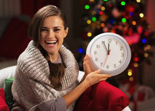 Jeune femme de sourire près de l'arbre de Noël montrant l'horloge Images libres de droits