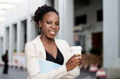 Jeune femme de sourire prenant le café dehors Photos libres de droits