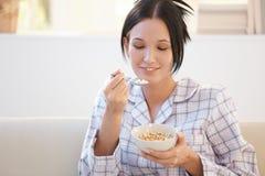 Jeune femme de sourire prenant le petit déjeuner de céréale Photographie stock libre de droits