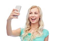 Jeune femme de sourire prenant le selfie avec le smartphone Image stock