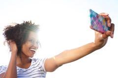 Jeune femme de sourire prenant le selfie avec le téléphone intelligent dehors contre la lumière du soleil lumineuse images libres de droits