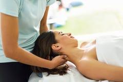 Jeune femme de sourire recevant un massage principal à un centre de station thermale Photographie stock