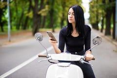 Jeune femme de sourire regardant son téléphone portable, se reposant sur le scooter photographie stock