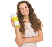 Jeune femme de sourire retenant la cuvette de café Image stock